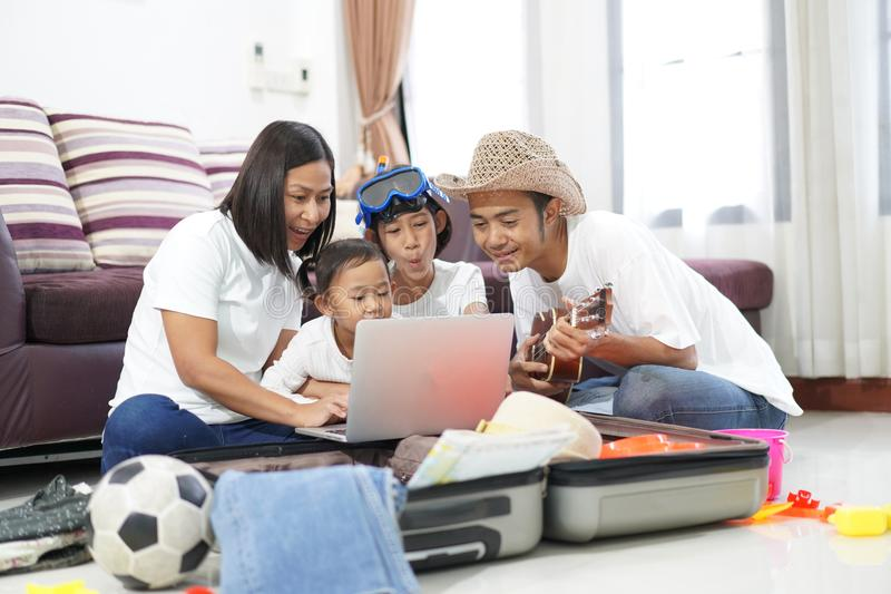 Happy asian family on a floor at home planning vacation travel t. Rip togetherness relaxation concept royalty free stock photos