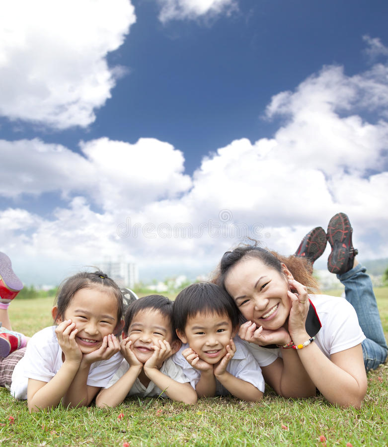 Happy asian family on the grass. With cloud background stock image