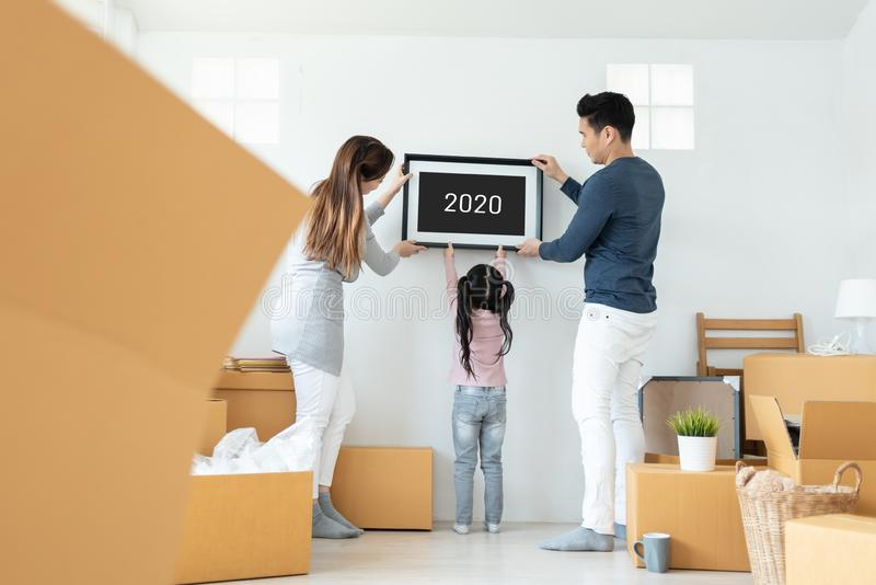 Happy Asian family picture holding frame during moving house together. Happy Asian family holding a picture frame during moving house together. 2019 to 2020, New royalty free stock photo