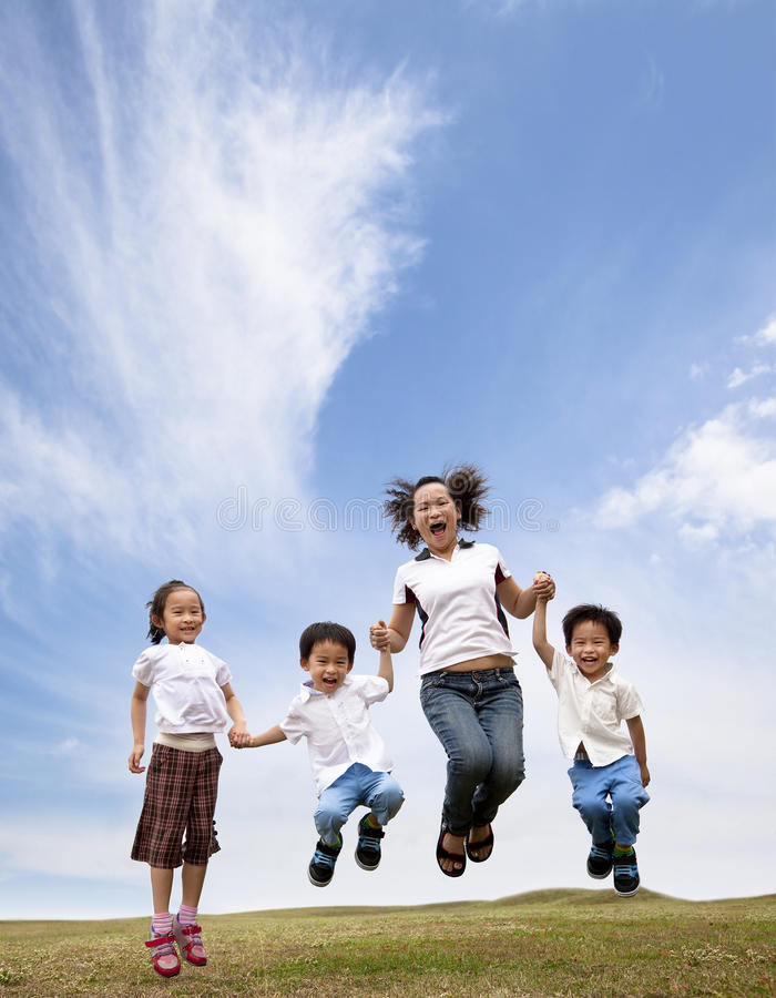 Happy asian family jumping on the grass. Field. mother and her children stock photo