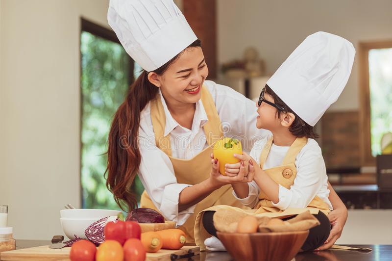 Happy Asian family in kitchen. Mother and son in chef hat preparing food in home kitchen together. People lifestyle and Family. stock image