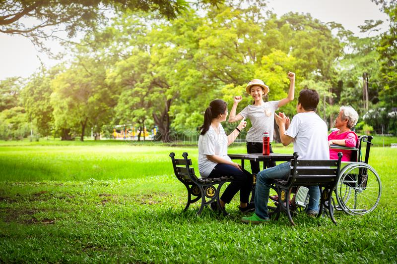 Happy asian family in outdoor park,father,mother with little child girl or daughter play,dancing,singing,elderly woman having fun, royalty free stock images