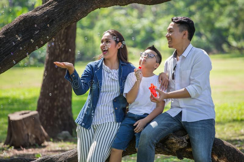 Happy asian Family, parents and their children blowing soap bubbles  in park together. father, mother ,son sitting on branch of. Big tree  having fun and royalty free stock image