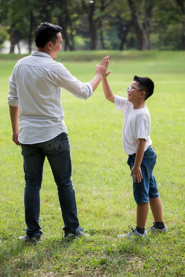 happy asian Family, parents and their children give high five  in park together. father supporting son outside . Support helping stock photo