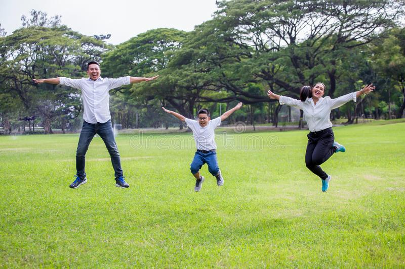 happy asian Family, parents and their children jumping together in park . father mother and son having fun and laughing outdoors stock photography