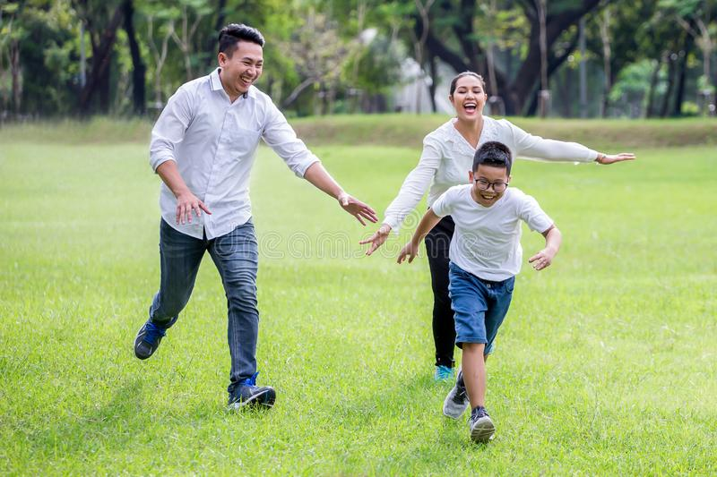happy asian Family, parents and their children running around  in park together. father mother and son having fun and laughing stock photo