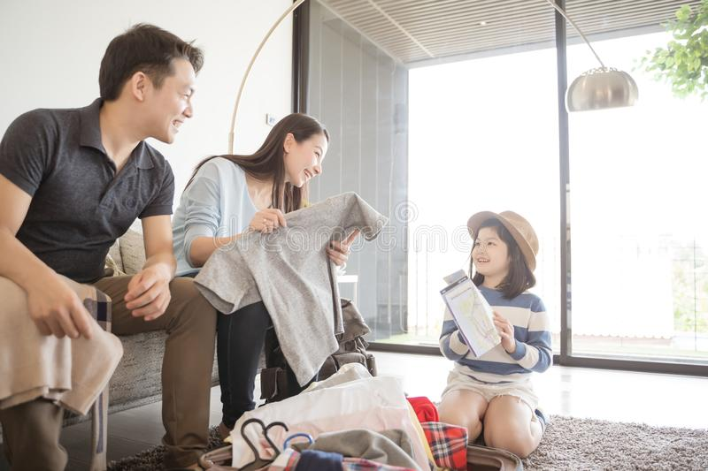 Happy Asian family is preparing for travel at home .Mom daughter and father are packing suitcases for the trip stock images