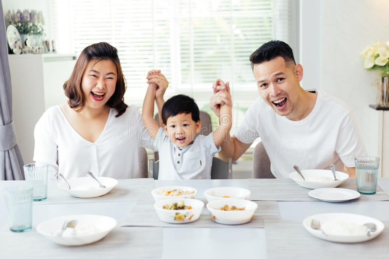 Happy Asian family raising child`s hands up and smiling while having a meal together. royalty free stock photography