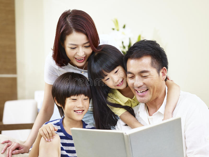 Happy asian family reading a book at home stock photography