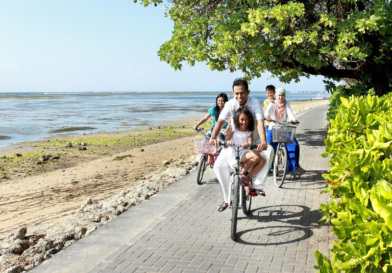 Happy asian family riding bikes in the beautiful morning at the stock photo