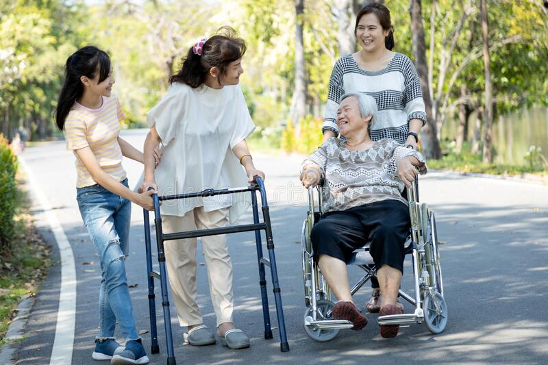 Happy asian family,senior woman, disabled grandmother with walker and wheelchair, daughter,teen granddaughter enjoying a walk in stock photos
