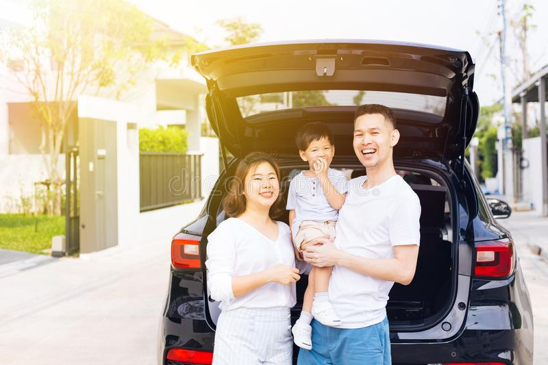 Happy Asian family standing on the back of SUV car with smile and happiness. royalty free stock photo