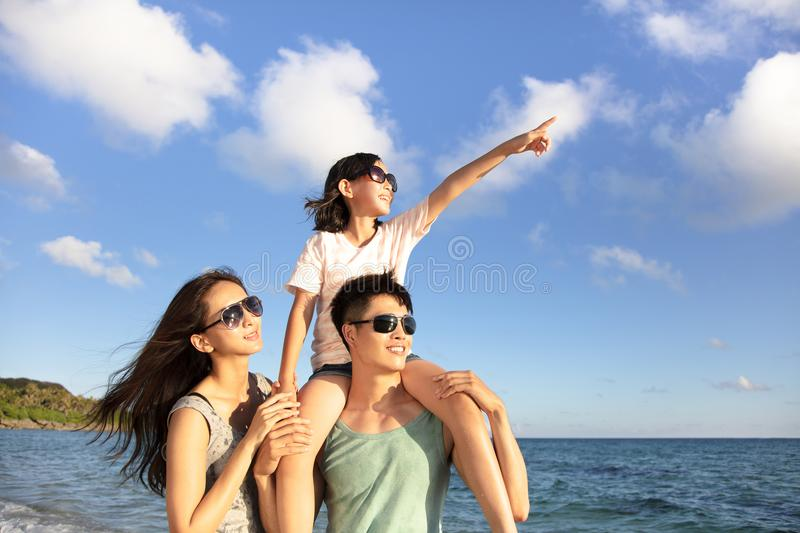 Happy family standing on the beach watch the sunset. Happy asian family standing on the beach watch the sunset royalty free stock photography