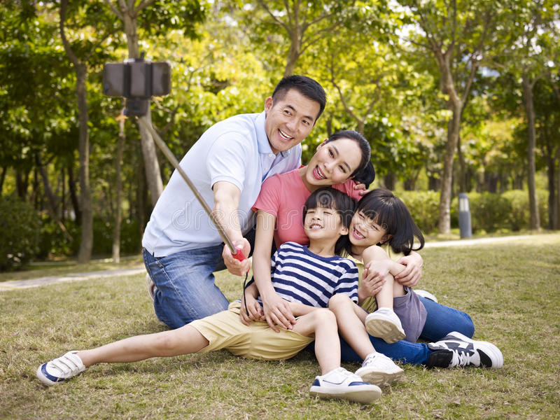 Happy asian family taking a selfie. Happy asian family with two children taking a outdoor selfie with selfie stick in a city park stock photos