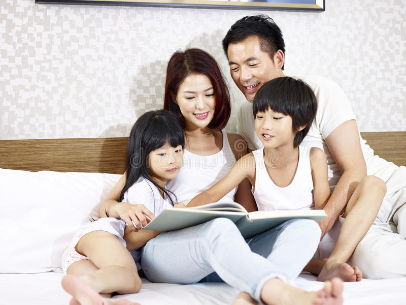 Asian family with two children reading book in bedroom. Happy asian family with two children sitting in bed reading a book together royalty free stock photography