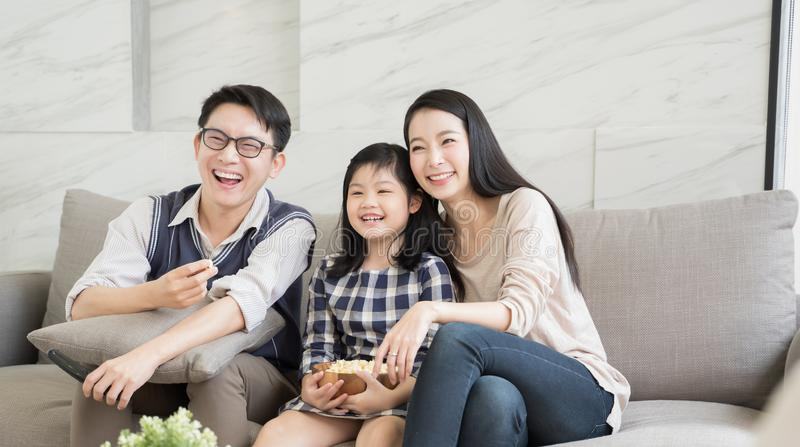 Happy asian family watching tv together on sofa in living room. family and home concept. royalty free stock images