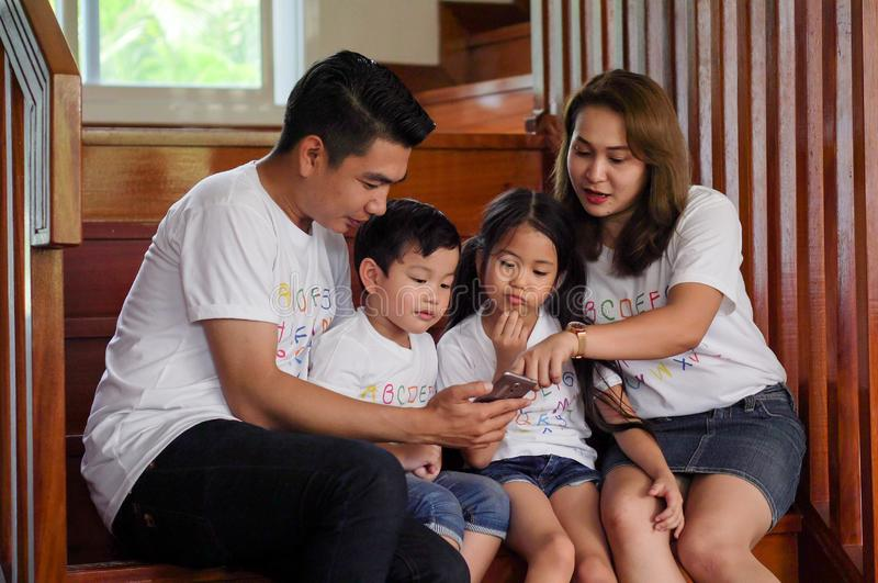 happy asian Family watching video on mobile phone at home together. father,mother ,son,daughter using smartphones on stair. royalty free stock photos