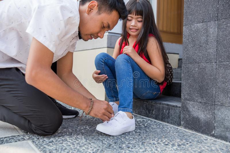 Help his daughter to put on her shoes stock image