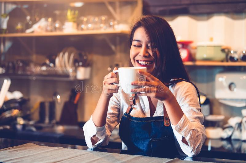 Happy Asian female barista holding cup of coffee and tasting brewed coffee from herself with cafe restaurant background. Waitress. At cafeteria. Food and drink stock photo