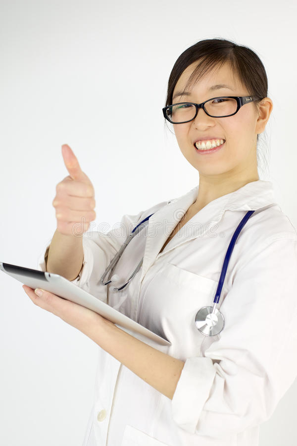 Happy asian female doctor thumb up with tablet stock photos