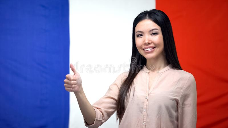Happy Asian female showing thumbs-up against French flag background, template royalty free stock photo