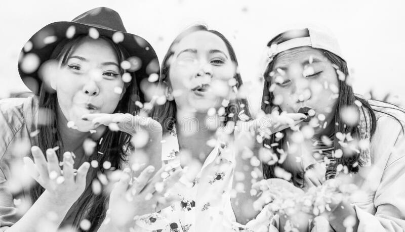Happy Asian friends having fun throwing confetti outdoor - Young trendy people celebrating at festival event outside. Friendship, fest, entertainment and stock photography