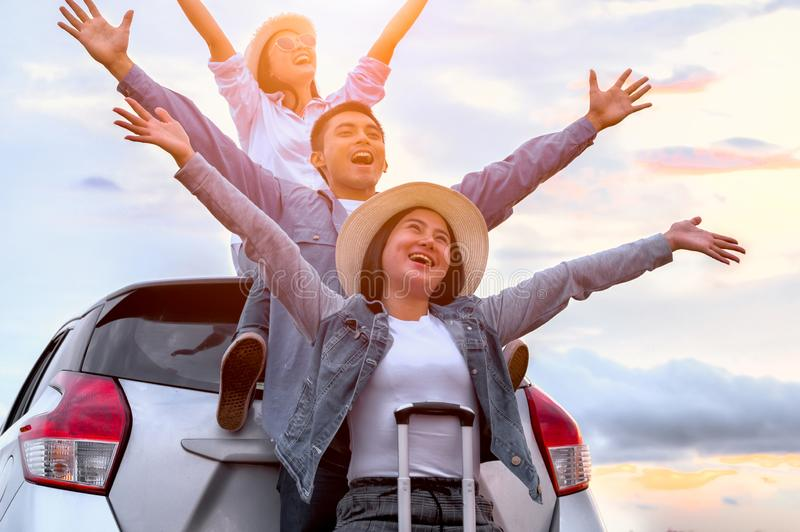 Happy Asian friends spread arms widely and breathed fresh air with happiness mood in on raod trip in car trunk. People lifestyle. In long vacation trip concept stock photography