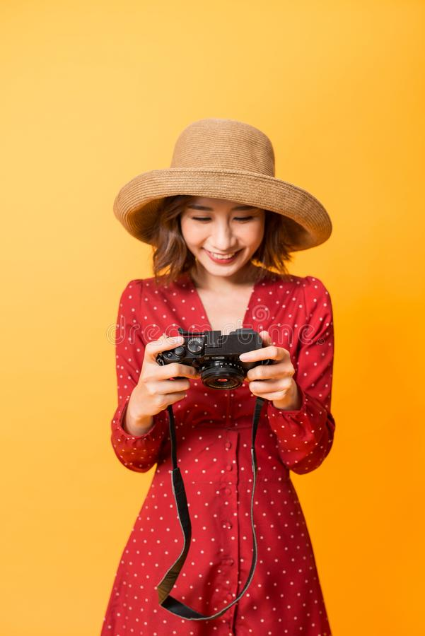 Happy Asian girl checking photos on her camera while wearing red dress and hat isolated on orange background royalty free stock photo