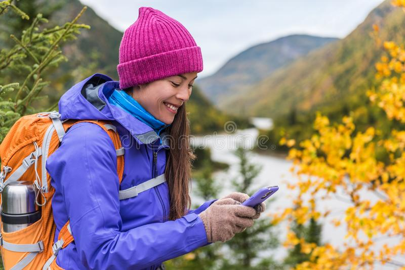Happy asian girl in cold weather gear hiking in nature using smartphone with touch screen gloves during hike in autumn travel royalty free stock photo