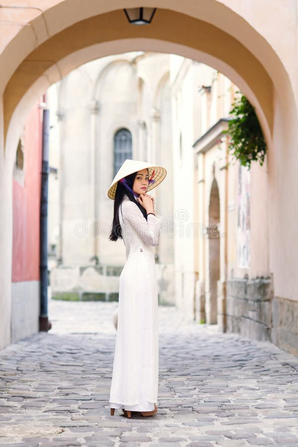 Happy asian girl dressed in traditional Ao Dai white dress with vietnamese conical hat Non La, Leaf Hat. royalty free stock photo