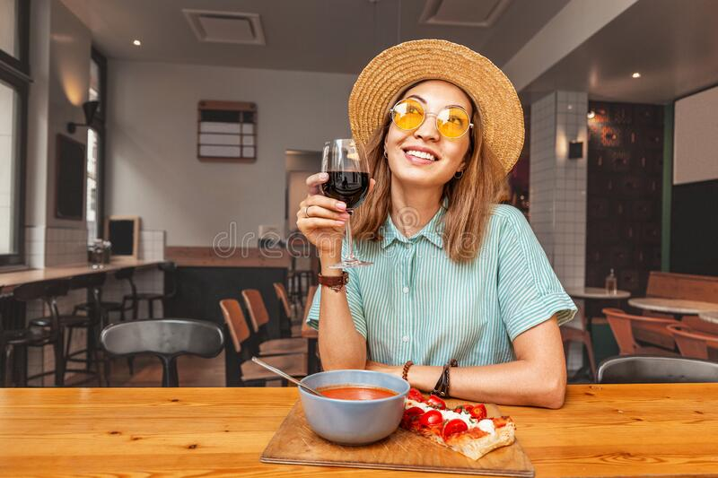 Asian girl eating in restaurant and drinking red wine. Italian or Spanish cuisine. Happy Asian girl eating in restaurant and drinking red wine. Italian or stock image