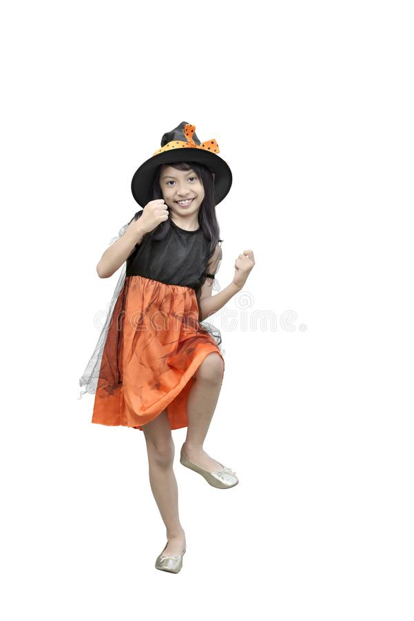 Happy asian girl with halloween witch costume posing. Isolated over white background royalty free stock image