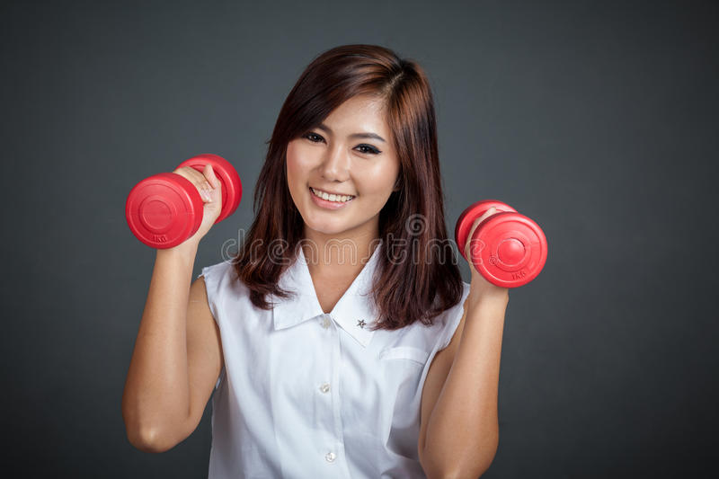 Happy Asian girl hold dumbbells with both hand. On gray background royalty free stock image