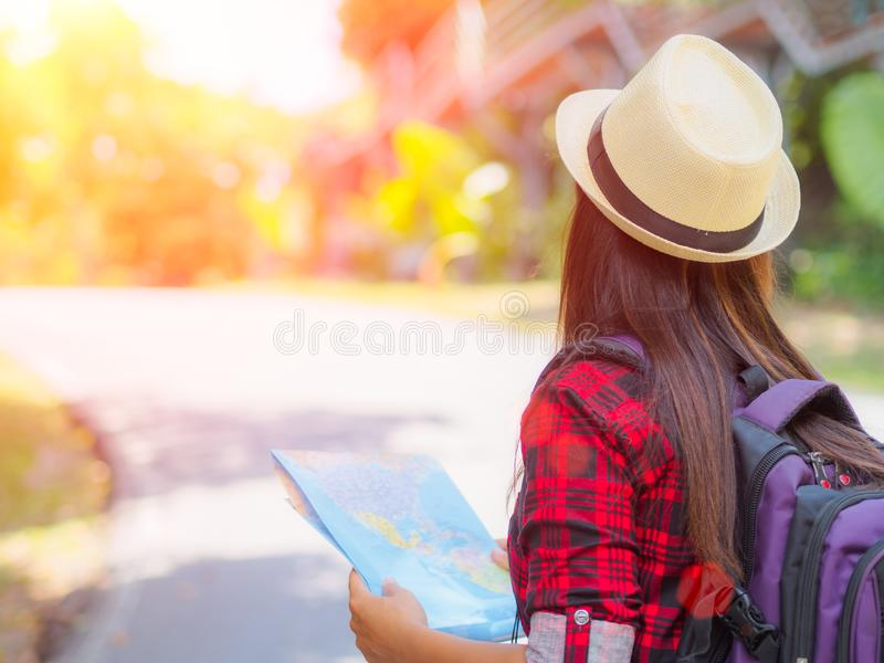 Happy Asian girl holding map with backpack in the road and forest background stock images