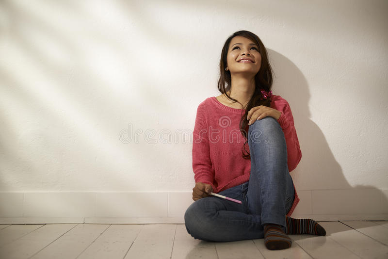 Happy Asian girl holding pregnancy test at home royalty free stock images