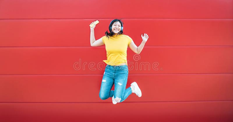 Happy Asian girl jumping while listening music outdoor - Crazy Chinese woman having fun dancing a song against red background stock photos