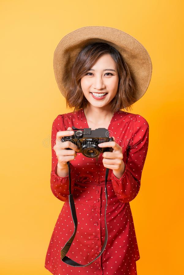 Happy Asian girl looking at her camera while wearing red dress and hat  on orange background stock image