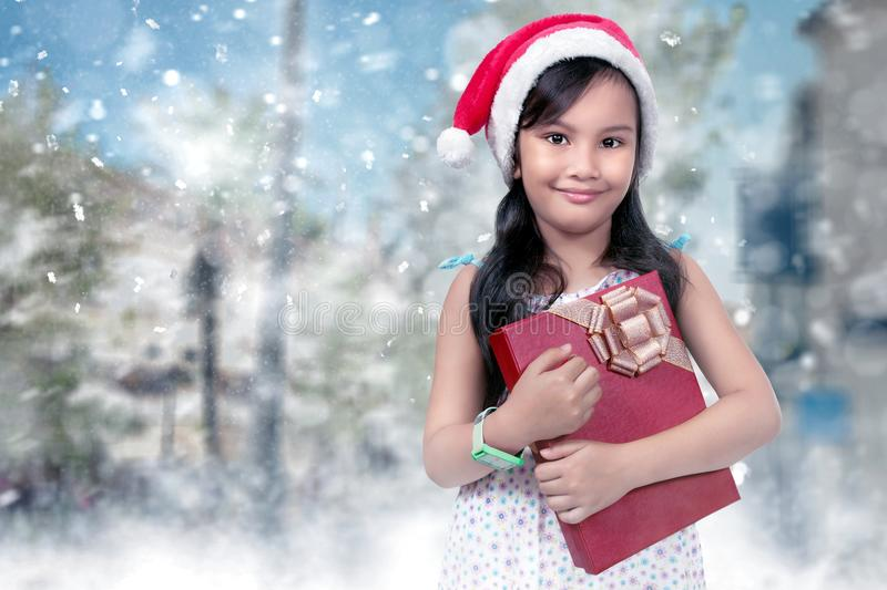 Happy asian girl in red santa hat with xmas gift stock images