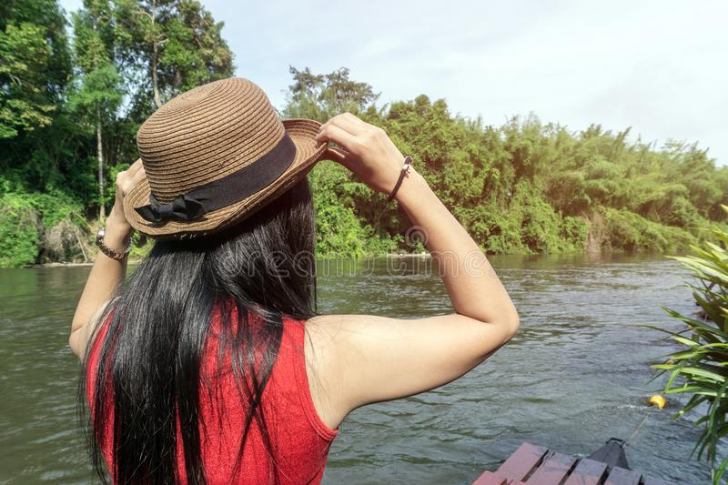 Happy Asian girl red shirt and brown hat on the river in nature background stock photos