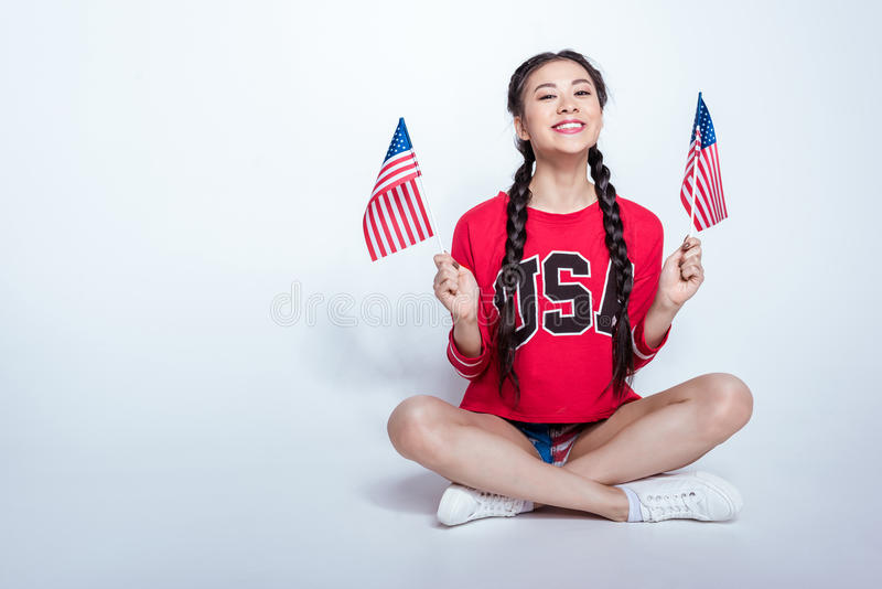 Happy asian girl in red sweatshirt with USA word sitting and holding little american flags isolated on grey stock photography
