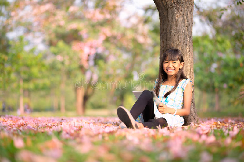 Happy asian girl. Sitting on grass with tablet computer in the park stock photography