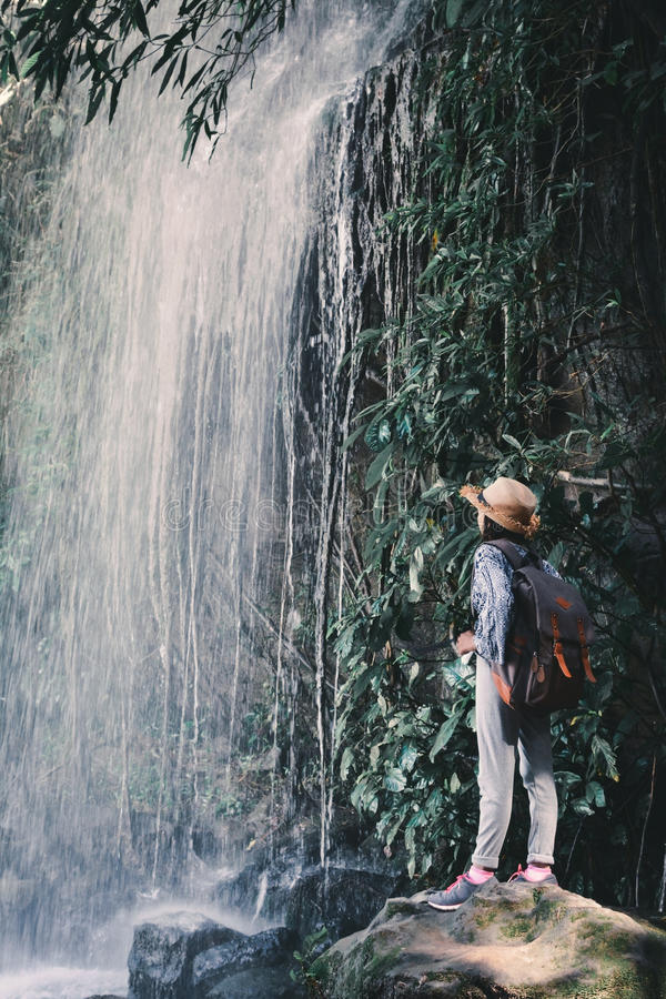 Happy Asian girl standing on stone and waterfall background stock photos
