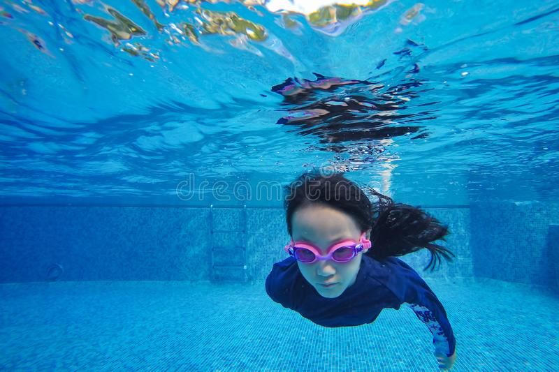 Happy asian girl swim and dive underwater, summer family vacation with child,relax,fun activity stock image