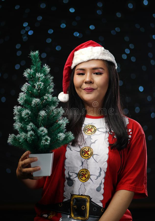 Happy Asian Girl Wearing Santa Costume Holding Small Christmas T stock photography