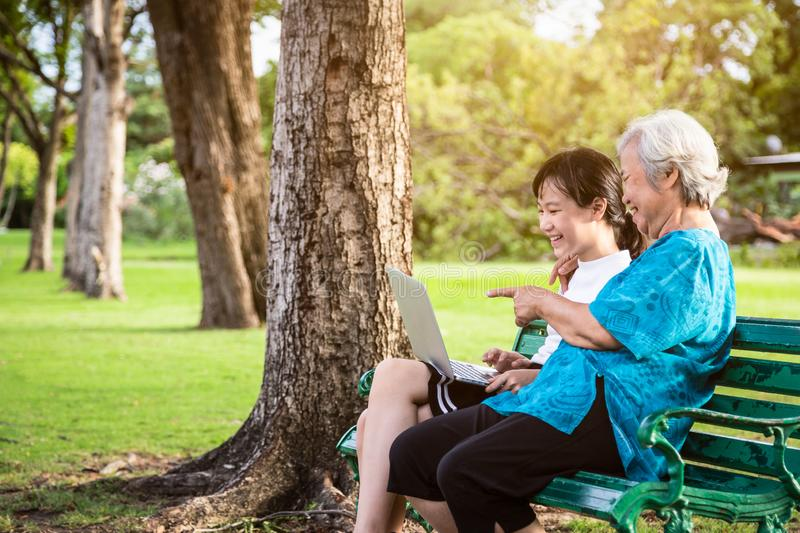 Happy asian granddaughter enjoy smiling and senior grandmother with laptop computer,child girl watching something or teaching and. Showing new computer royalty free stock photography
