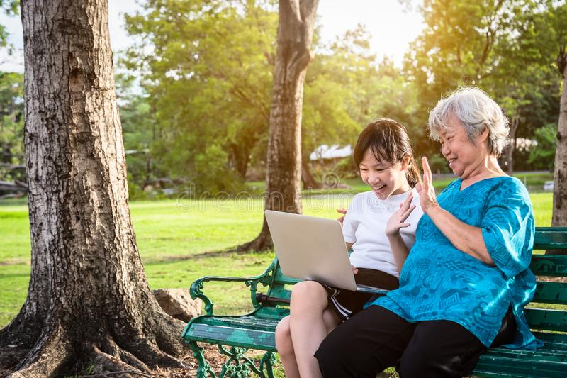 Happy asian granddaughter enjoy smiling and senior grandmother using video conferencing with laptop computer,cheerful child girl. Having video call,waving her stock images