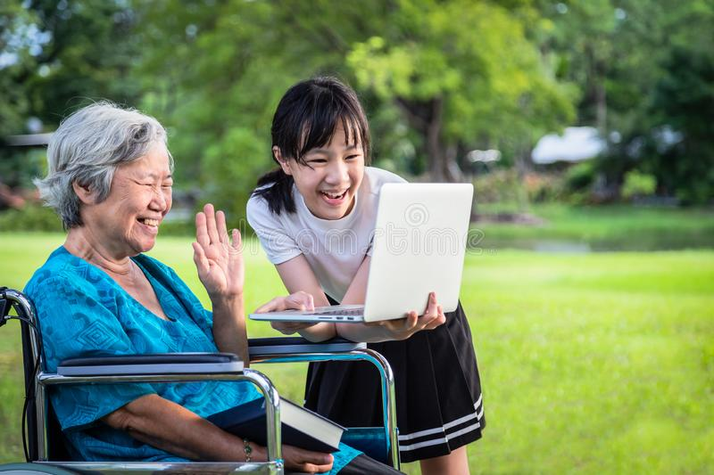 Happy asian granddaughter enjoy smiling and senior grandmother using video conferencing with laptop computer,child girl having royalty free stock photos