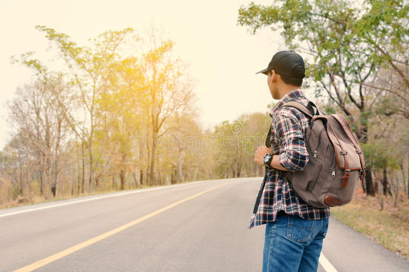 Happy Asian hipster man backpack. In nature background, Relax time on holiday concept travel , color of vintage tone and soft focus royalty free stock image