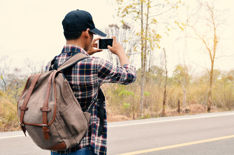 Happy Asian hipster man backpack. In nature background, Relax time on holiday concept travel , color of vintage tone and soft focus stock photo