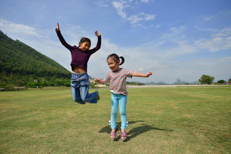 Happy Asian kids jumping with green grass royalty free stock image